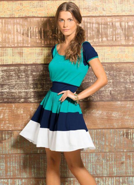 Modelo veste vestido nos tons de azul forte, verde claro e branco.
