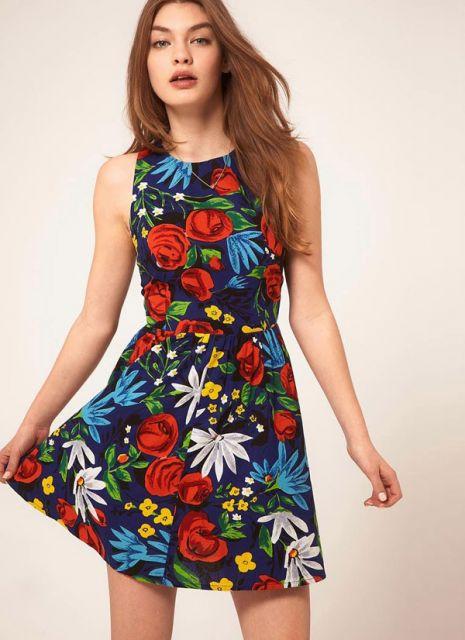 Modelo usa vestido floral, nos tons de preto,azul, branco, vermelho, amarelo.