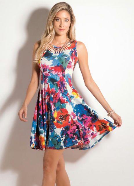 Modelo usa vestido estampado em tons de azul, branco, vermelho e amarelo, modelo regatinha.