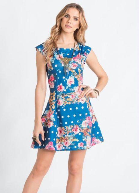 Modelo usa vestido azul com flores rosas e bolinhas brancas.