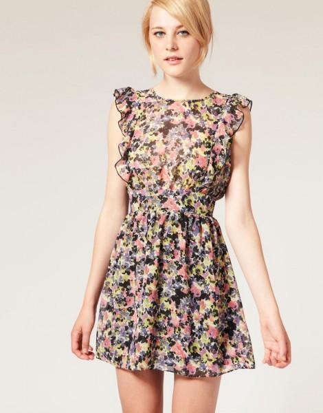 Modelo usa vestido estampado nos tons de preto, rosa, roxo e amarelo clarinho