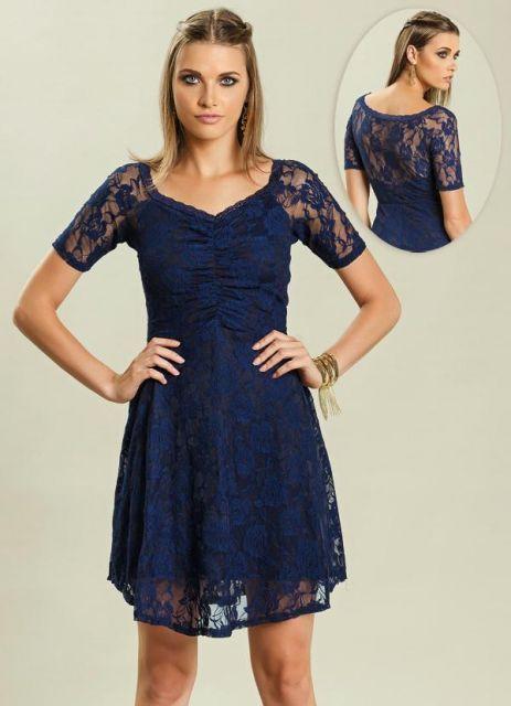Modelo usa vestido azul marinho, com manguinhas de renda.