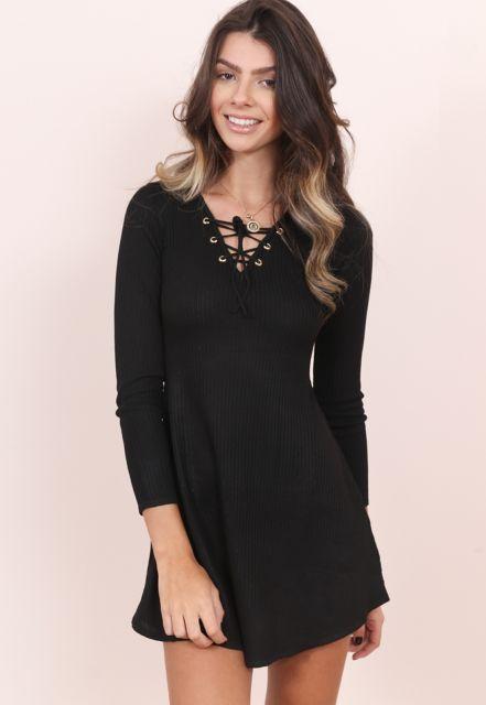 Modelo usa vestido preto evasê com detalhe no decote, com ilhós.