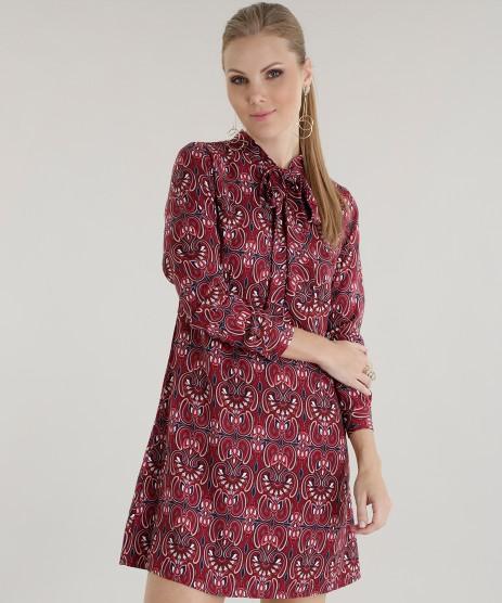 Modelo usa vestido estampado em vermelho, manga longa.