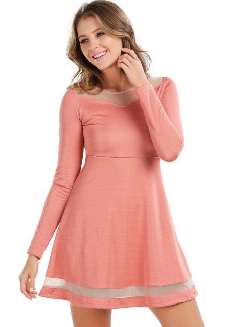 Modelo usa vestido na cor salmão com transparências, no decote e na borda sa saia do vestido.