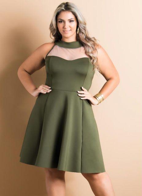 Modelo veste vestido verde musgo, com detalhe de tule no decote.