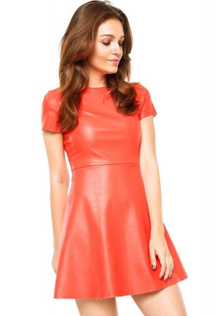 Modelo usa vestido laranja de manguinhas em couro sintético.