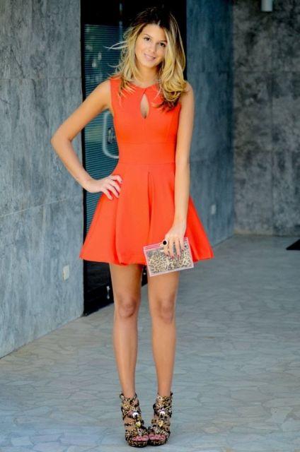 Modelo usa vestido laranja, com detalhe no busto, sandalia amarrações preta e bolsa de mao prata.