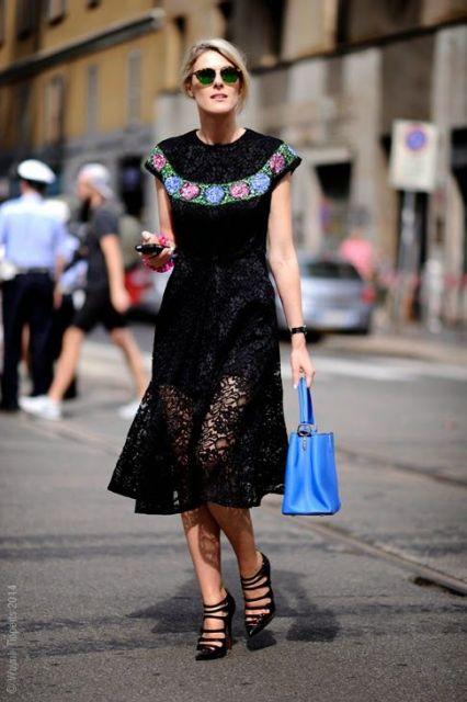 Modelo usa sandália pesada preta e vestido preto de renda com decote todo fechado com bolsa de mão azul.