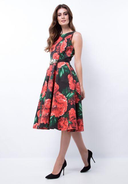 Modelo usa vestido midi godê, estampado em preto e vermelho, scarpin preto.