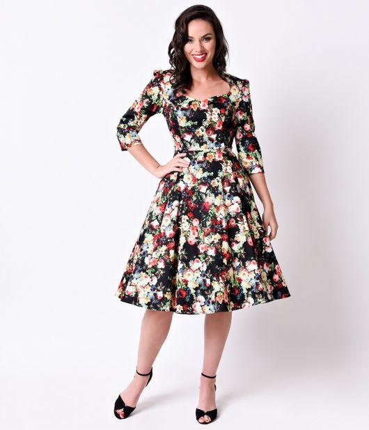 Modelo usa vestido preto com estampa floral bege e sandalia preta.