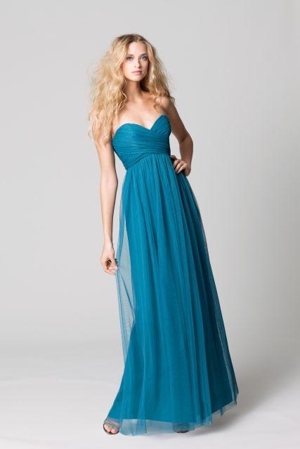 Modelo usa vestido azul voal, tomara que caia com decote.