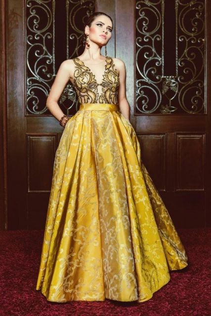 Modelo usa vestido amarelo, godê com busto elaborado.