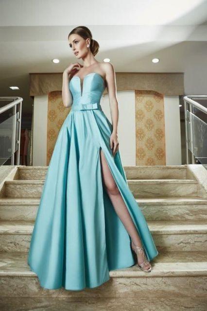 Modelo usa vestido azul tomara que caia longo de fenda, com sandalia prata.