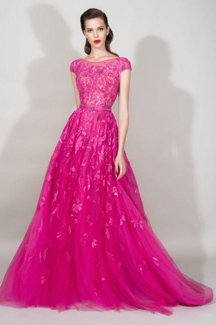 Modelo veste vestido rosa longo, de mangas e decote fechado.