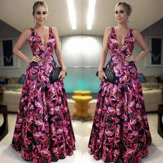 Modelo usa vestido longo, estampado em rosa e preto, com carteira de mão preta e cabelos presos.