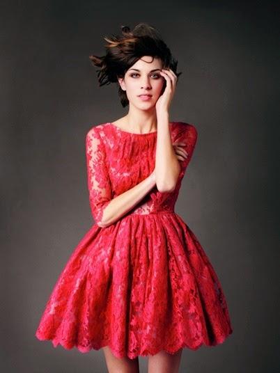 Modelo usa vestido godê vermelho, meia manga de renda.