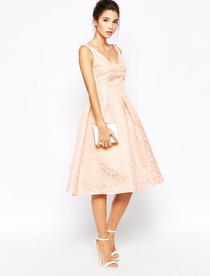Modelo veste vestido rosê clarinho, sandalia branca e bolsa de mao prata.