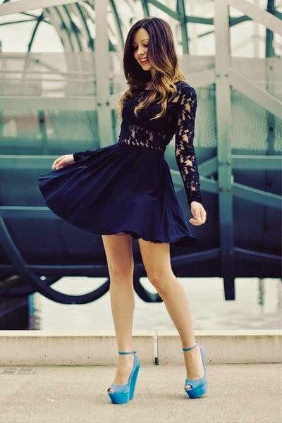 Modelo usa vestido preto com renda no busto, sapato azul claro e cabelos soltos.
