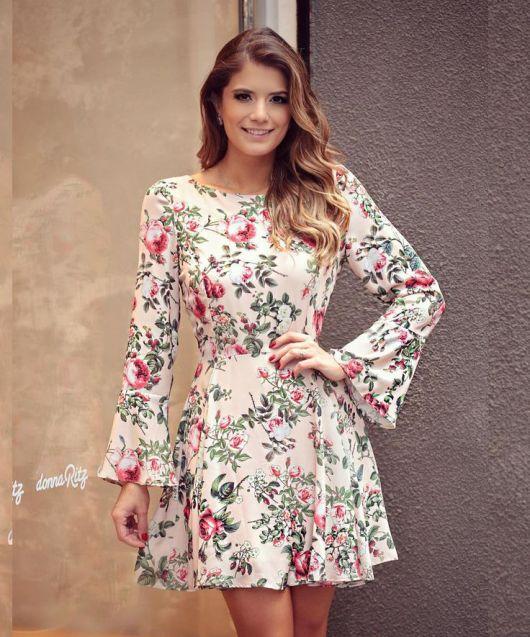 Modelo usa vestido branco estampado em florais, com manga flare.