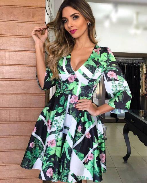 Modelo com vestido nas cores verde, preto, rosa e branco estampado com decote.