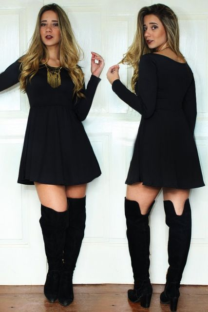 Modelo usa vestido preto com bota no mesmo tom.