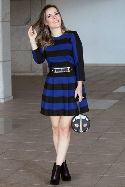 Modelo usa vestido listrado em azul e preto, bolsa de mao e ankle boot preta.