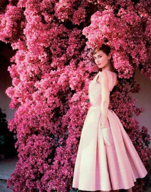 Haudrey Hepburn de vestido rosa godê, em arvore com flores cor de rosa.