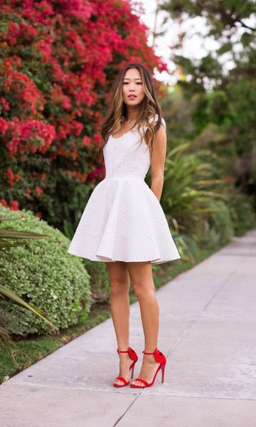 Modelo usa vestido branco simples, com sapato salto vermelho.