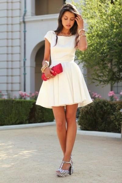 Modelo usa vestido branco de manga curto com sandalia salto largo cinza e bolsa de mão vermelha.