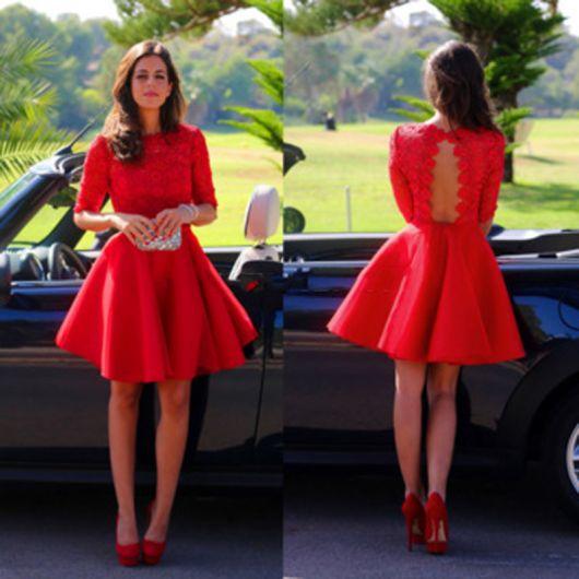 Modelo veste vestido gode vermelho, rodado meia manga com detalhe nas costas, bolsa prata de mao e sapato vermelho bonequinha.