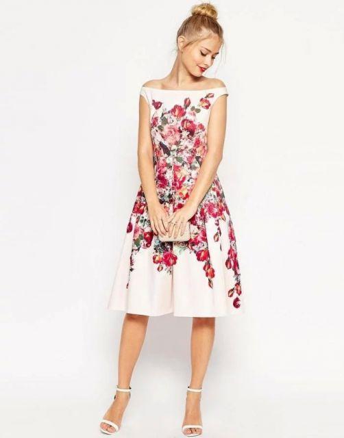 Modelo usa vestido branco com estampa floral vermelha.