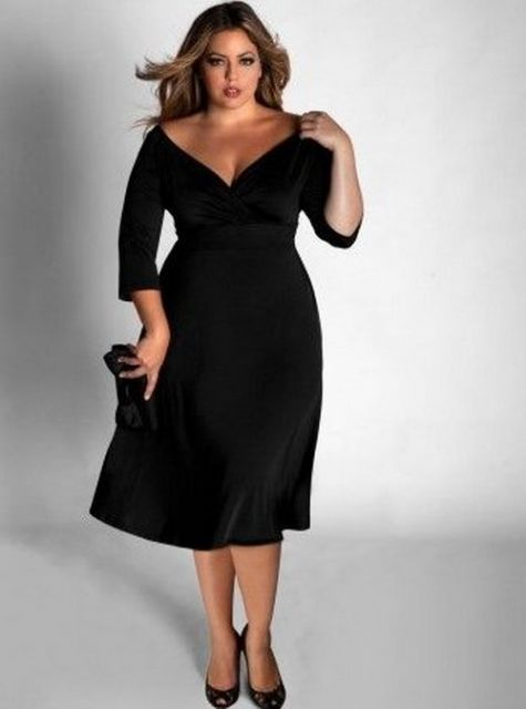 Modelo plus size usa vestido preto abaixo do joelho com decote V.