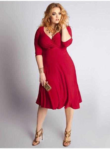 Modelo plus size usa vestido vermelho abaixo do joelho com sandália tons terra.