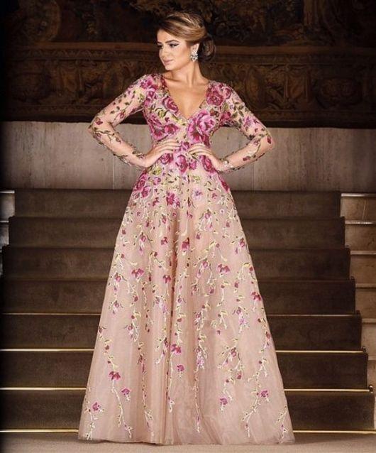 Modelo usa vestido bordado nos tons de nude com bordados em rosa e decote v, cabelo preso.