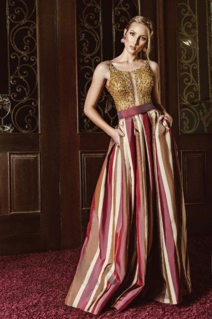 Modelo usa vestido godê com busto em renda dourada, e saia com listras verticais em tons de vermelho e dourado.