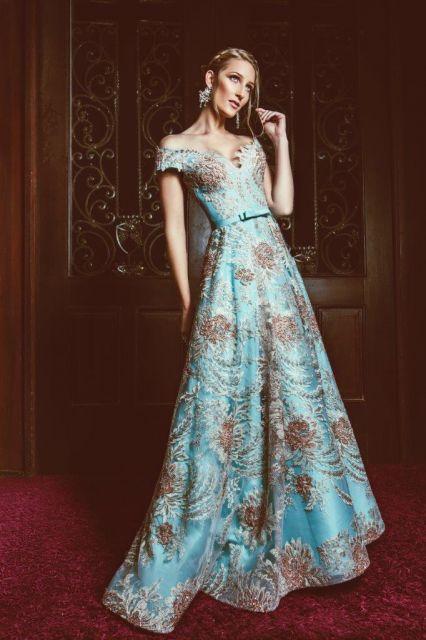 Modelo veste vestido azul com estampas e cabelo preso.