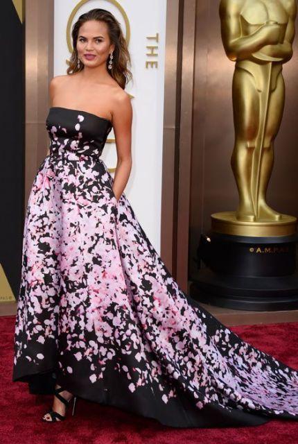 Modelo usa vestido tomara que caia longo, estampado em cores preto e rosa.