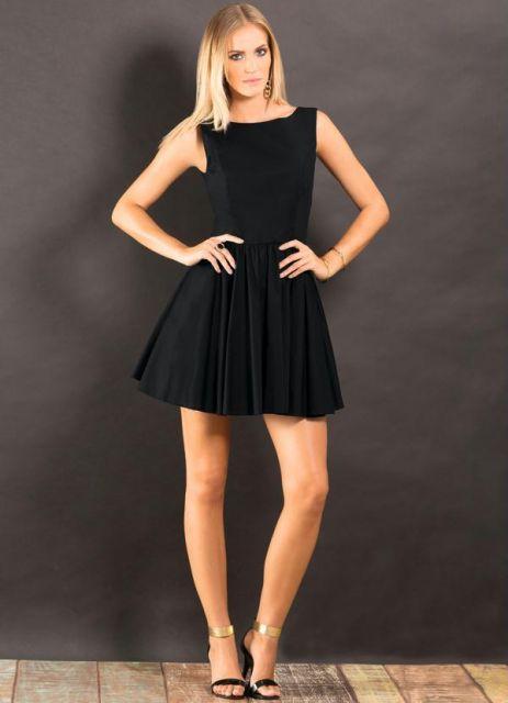 Modelo com vestido preto curto e sandália de salto preta.