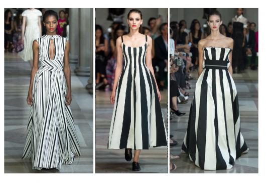 Modelos vestem vestido listrado preto e branco em desfile.
