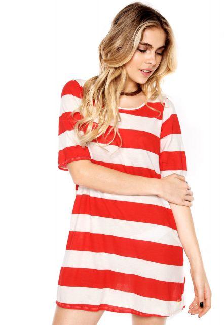 Modelo com vestido estilo camisa listrado na cor de branco e vermelho.