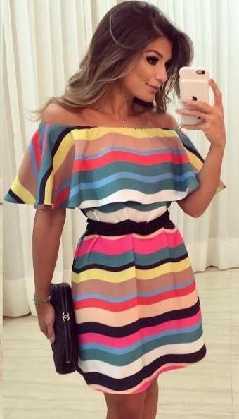 Modelo veste vestido listrado em tons de azul, amarelo, rosa, amarelo e preto com branco.
