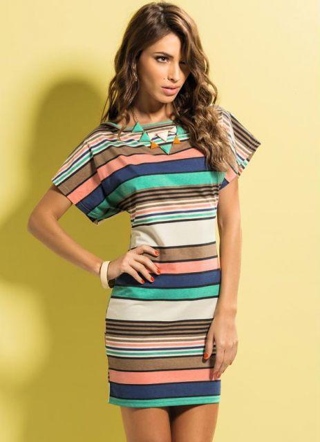 Modelo usa vestido listrado nas cores rosa, verde, marrom e azul com colar no tom de verde do vestido.