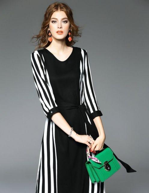 Modelo com vestido listrado em preto e branco, brinco laranja e bolsa de mão verde.
