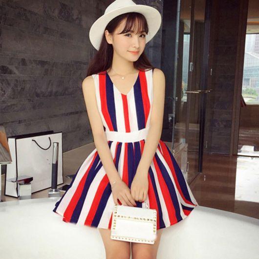 Modelo veste look com vestido listrado nas cores branco, vermelho e azul, bolsa de mao e chapeu branco.