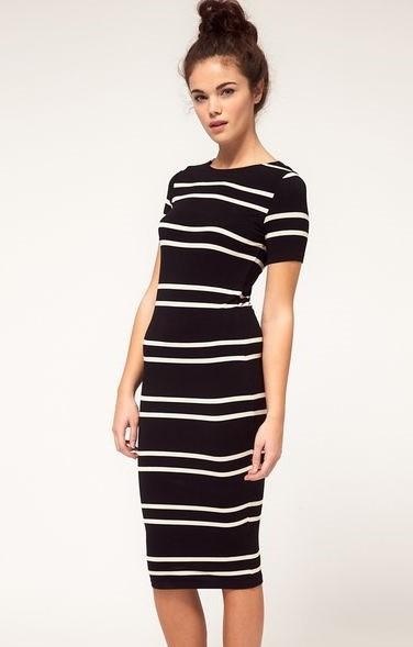 Modelo veste vestido preto midi nas cores de preto e branco.
