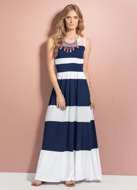 Modelo veste vestido nas cores azul e branco longo modelo listrado.
