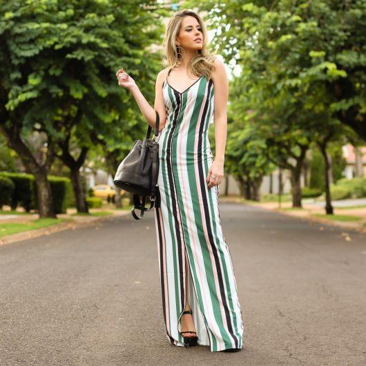 Modelo veste vestido longo com listras verdes na vertical, sandalia preta e bolsa de mao no mesmo tom.