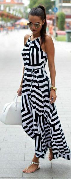 Vestido listrado em tom de branco e preto, com bolsa de mao branca.