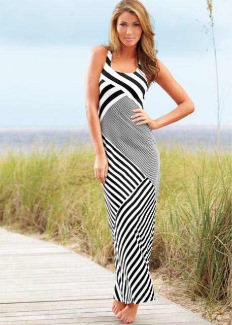 Look com vestido preto e branco longo com listras diagonais em diferentes espessuras.
